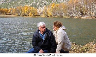 Happy elderly couple sitting and ta