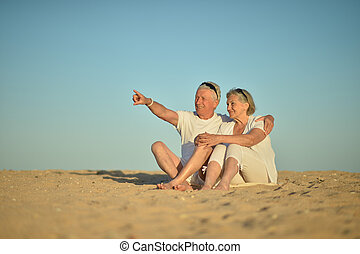 Happy elderly couple sitting on tropical beach. man pointing