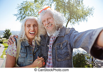 Happy elderly couple taking selfies