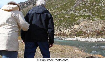 Happy elderly couple walking along
