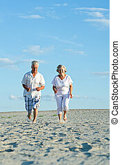 Happy elderly couple walking barefoot on the sand in the...
