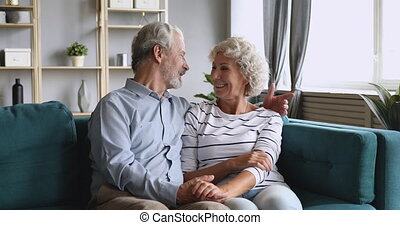 Happy elderly grandparents couple chatting embracing relaxing on couch