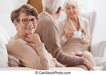 Happy elderly lady enjoying time spent with her family by a...