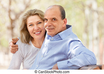 happy elderly man and woman hugging on a bench