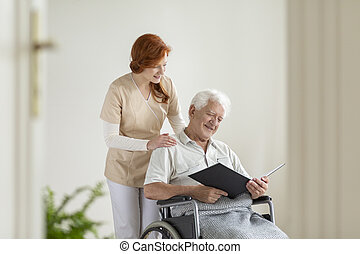 Happy elderly man in the wheelchair reading book during visit of caregiver at home