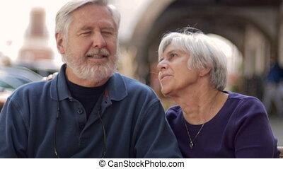 Happy elderly man kisses his elderly wife on the cheek