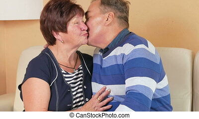 Happy elderly man returns home and embraces his beloved wife on a sofa in a beautiful house. They kiss, talk and laugh.