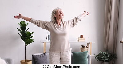 Excited middle aged 70s beautiful healthy woman standing with outstretched arms, feeling emotional indoors. Happy elderly mature grandmother welcoming new day, doing morning stretching exercises.