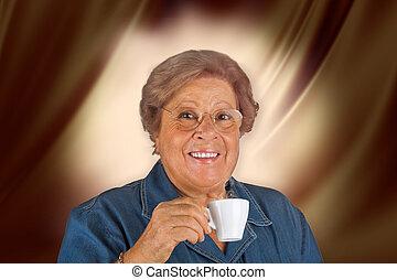 Happy elderly woman drinking coffee