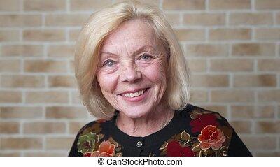 Happy elderly woman - Happy smiling elderly woman peering...