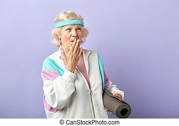 Happy elderly woman holding a yoga mat