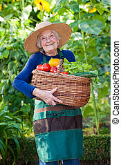 Happy Elderly Woman Holding Basket of Vegetables