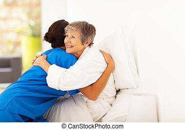 elderly woman hugging caregiver - happy elderly woman...