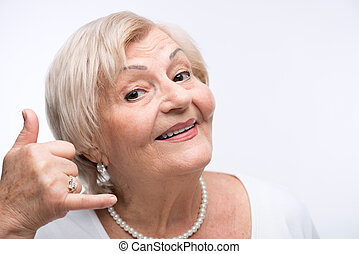 Happy elderly woman imitating a telephone call