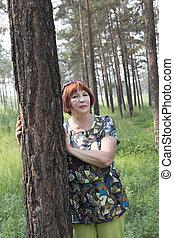 Happy elderly woman in a summer park.