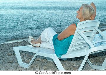 Happy elderly woman on beach