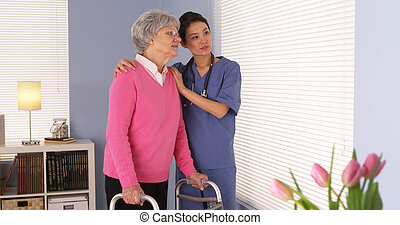Happy elderly woman patient talking with Asian nurse