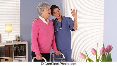 Happy elderly woman patient talking with Asian nurse