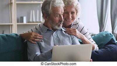 Happy elderly woman peeking from husband shoulder, looking ...