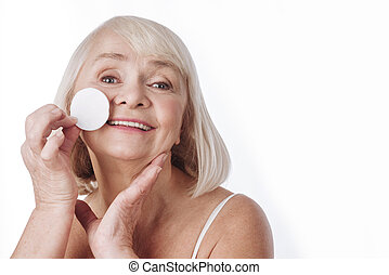 Happy elderly woman removing her make up