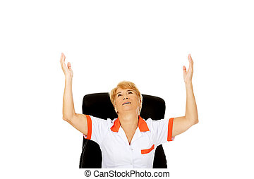 Happy elderly woman sitting behind the desk with hands up