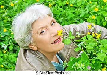 Happy elderly woman sitting on a glade of yellow flowers