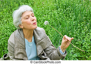 Happy elderly woman sitting on a meadow in spring green grass