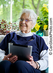 Happy Elderly woman sitting on a sofa looking at the camera and laughing while holding a tablet