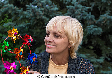 Happy elderly woman smiles and plays with propeller
