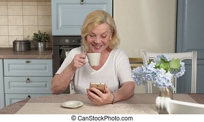 Happy elderly woman uses a smartphone - Happy mature woman...