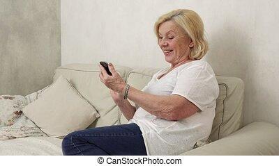 Happy elderly woman uses a smartphone