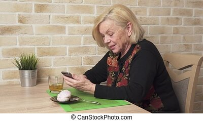Happy elderly woman using a smart phone - Happy elderly...