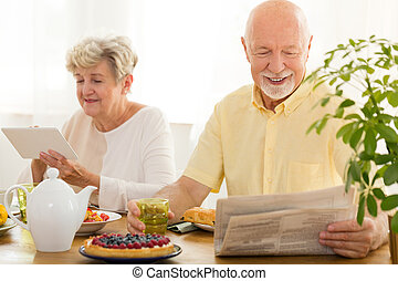 Happy elderly woman using tablet while her husband reading newspaper