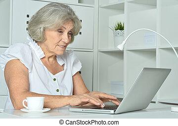 Elderly woman working on laptop