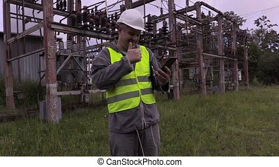 Happy electrician using tablet PC and laughing