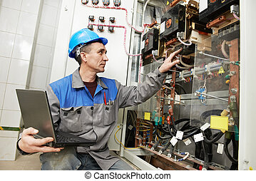 Happy electrician working at power line box - Smiling...