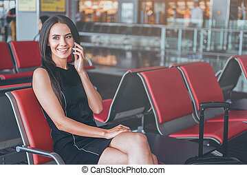 Happy elegant lady is sitting on bench at departure area