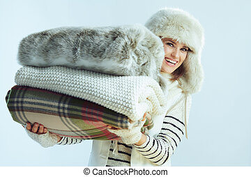 happy elegant woman holding stack of blankets