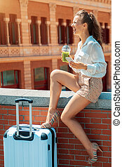 woman with green smoothie and smartphone looking into the distance