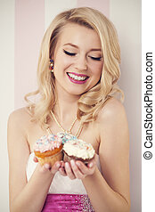 Happy elegant woman with muffins
