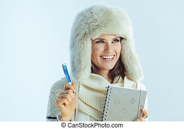 happy elegant woman with notebook and pen looking at copy space