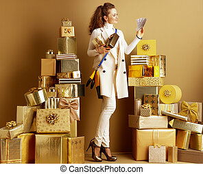 happy elegant woman with present boxes looking at money