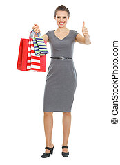Happy elegant woman with shopping bags showing thumbs up
