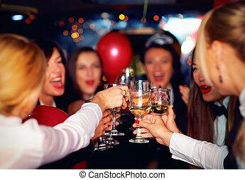 happy elegant women clinking glasses in limousine, focus on...