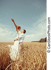Happy embracing couple on the wheat field background.