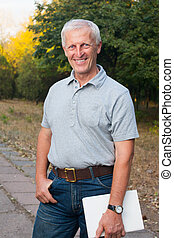 Happy emotional old man smiling. Posing in the park. Outdoor...