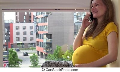 Happy emotional pregnant woman talking on her smartphone