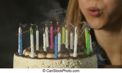 Happy emotional woman blowing out the candles on a birthday cake, candles extinguished