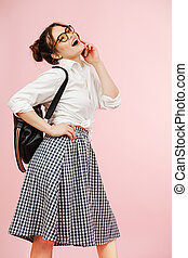Happy emotional young woman in a schoolgirl outfit chatting on the phone. Over pink background. She wears glasses, two buns on her head, checkered skirt and white dress shirt.