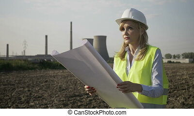 Happy engineer architect forewoman technician comparing work progress to layout on blueprint satisfied by professional achievement